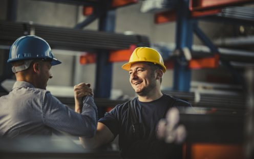 Happy metal worker greeting his manager in aluminum mill.